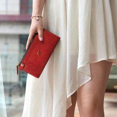 Foto de Modelo utilizando la billetera larga clásica con doble cierre y broches de cuero natural en color rojo solo para mujer
