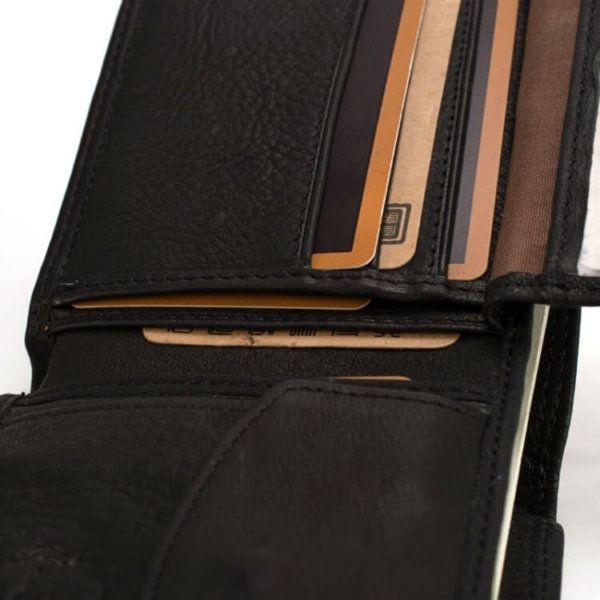 Foto que muestra en detalle el bolsillo secreto de la billetera clásica con monedero hecha de cuero natural, con una tarjeta dentro como ejemplo.