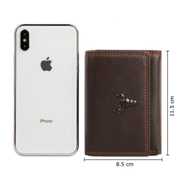 Foto de billetera clásica trifold de cuero natural mostrando tamaño de medidas y haciendo comparación con el tamaño de un IPHONE X