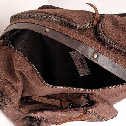 Foto de mochila crossbody vintage de lona y cuero mostrando su vista interior de bolsillo en color café