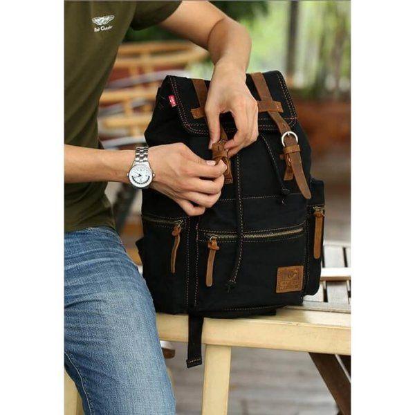Foto de modelo haciendo referencia en broches de mochila vintage urbana de lona y cuero en color negro
