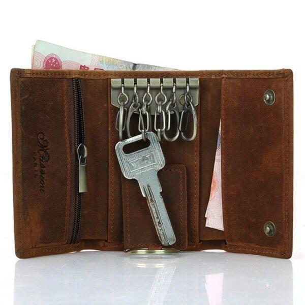 Foto donde se aprecia la función portallaves de la billetera estilo vintage y minimalista, hecha de cuero natural. Además de mostrar la capacidad de algunos de sus otros bolsillos en color marrón
