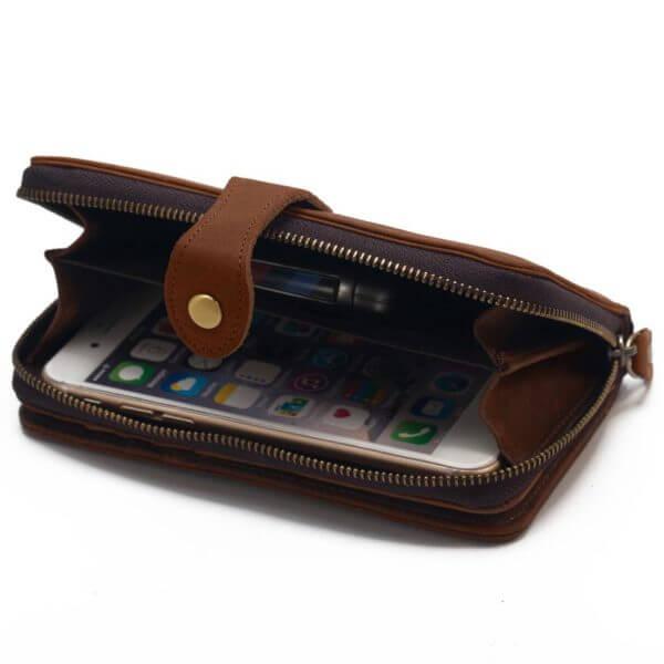 Foto donde se puede ver como un teléfono de 5 pulgadas entra facilmente en la billetera portacelular con broche y cierre, estilo vintage, hecha de cuero real.